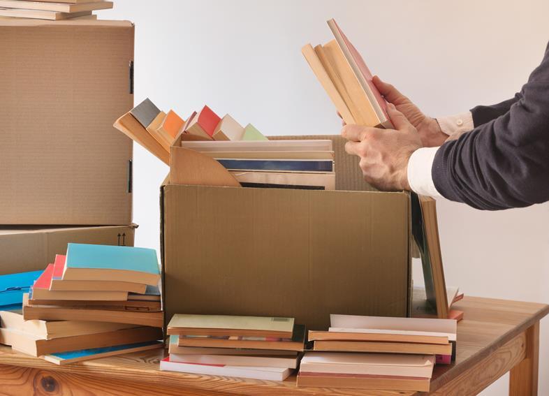 Klient pakuje książki do kartonów przed przeprowadzką